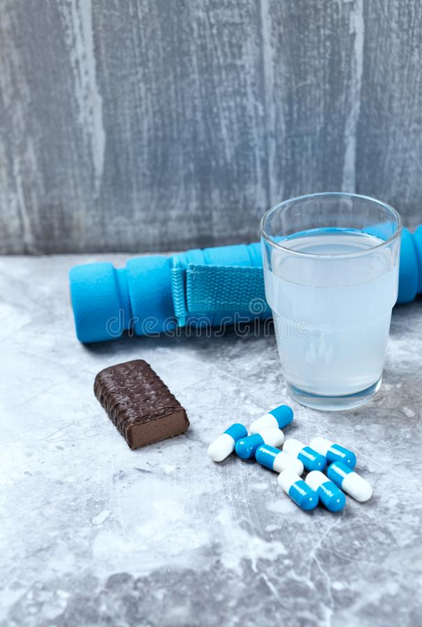 High Protein Bar, BCAA amino acids Drink, Creatine capsules and blue dumbbell in background. Sport nutrition. Stone / Wooden background. Copy space stock images