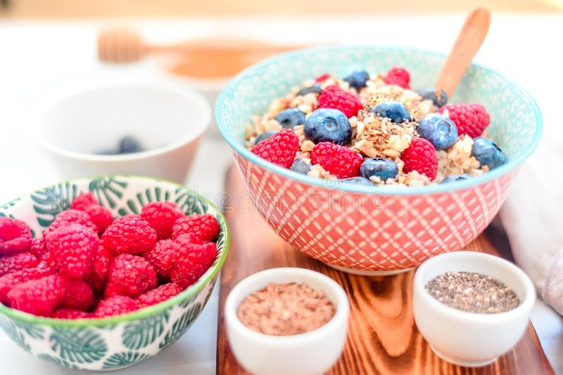 High protein healthy breakfast, buckwheat porridge with blueberries, raspberries, flax seeds and honey Closeup view, selective. High protein healthy breakfast royalty free stock images