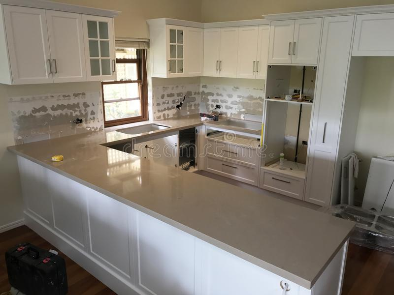 High Quality Extensive Kitchen Renovations. Extensive kitchen renovation with new stone bench tops, white cupboards, and white sub way tiles with wooden royalty free stock images