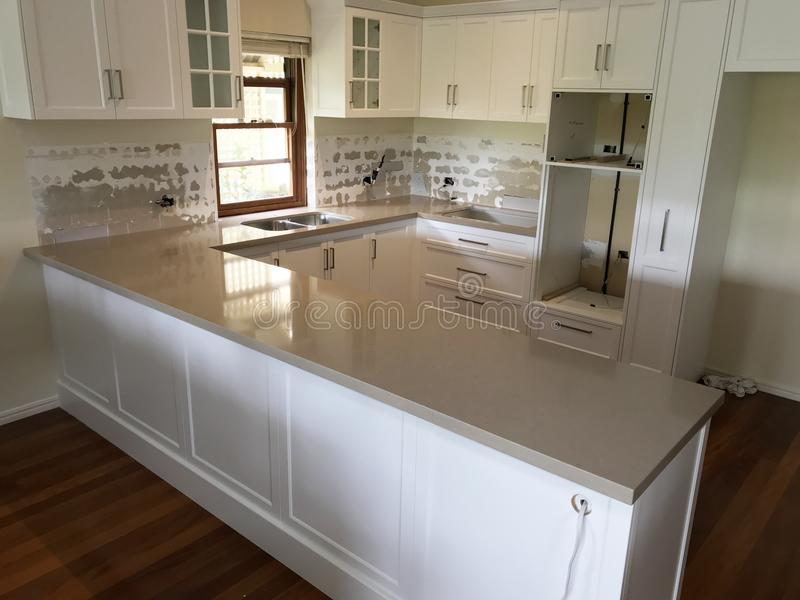 High Quality Extensive Kitchen Renovations. Extensive kitchen renovation with new stone bench tops, white cupboards, and white sub way tiles with wooden stock image