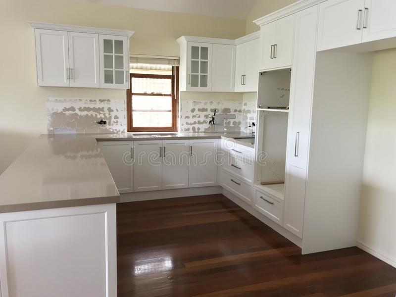 High Quality Extensive Kitchen Renovations. Extensive kitchen renovation with new stone bench tops, white cupboards, and white sub way tiles with wooden stock images