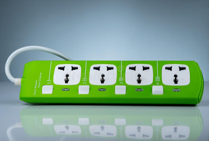 High quality and safety power strip with four electrical standard socket. Green universal plug with overload protection. Fire royalty free stock image