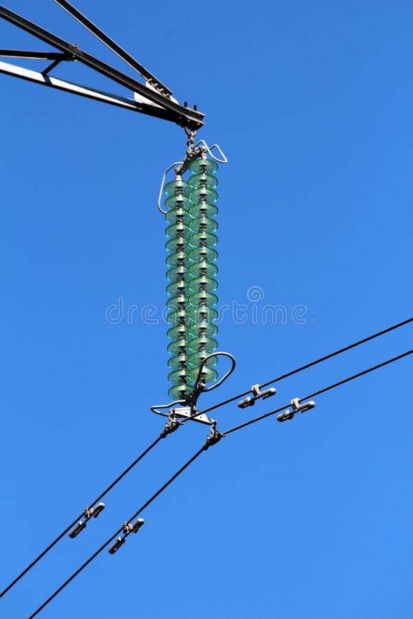 High quality tall glass power line utility insulators holding black electrical wires on strong metal utility pole on clear blue stock photography