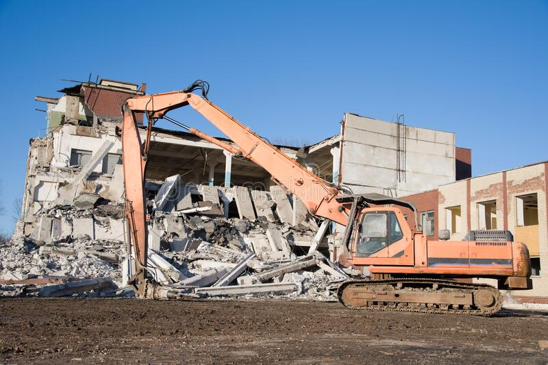 High Reach Excavator machines for demolition of tall building. Machine with hydraulic shears for demolish. Hydraulic Crushing Hammer destroys concrete of the royalty free stock image