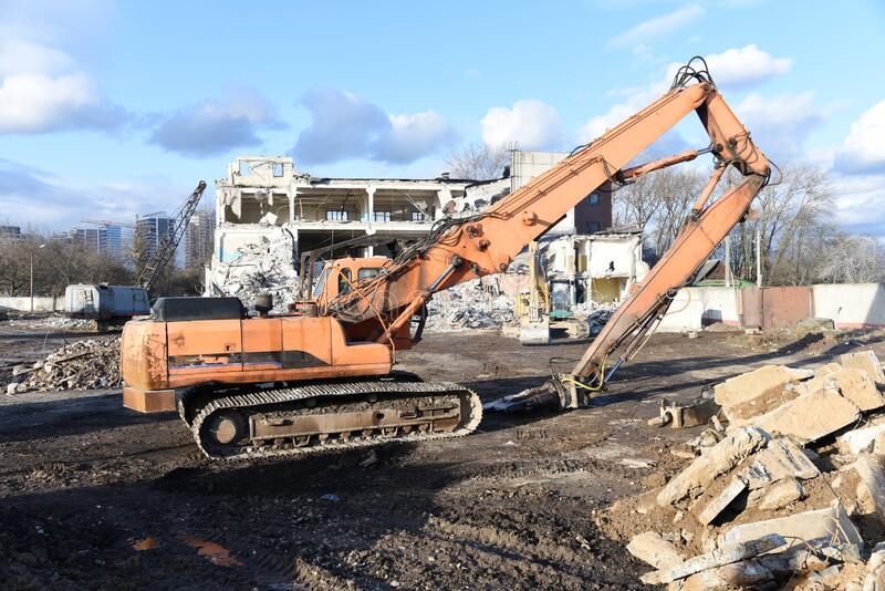 High Reach Excavator machines for demolition of tall building. Machine with hydraulic shears for demolish. Hydraulic Crushing Hammer destroys concrete of the stock images