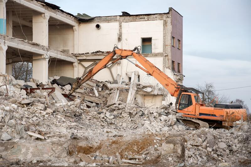 High Reach Excavator machines for demolition of tall building. Machine with hydraulic shears for demolish. Hydraulic Crushing Hammer destroys concrete of the royalty free stock images