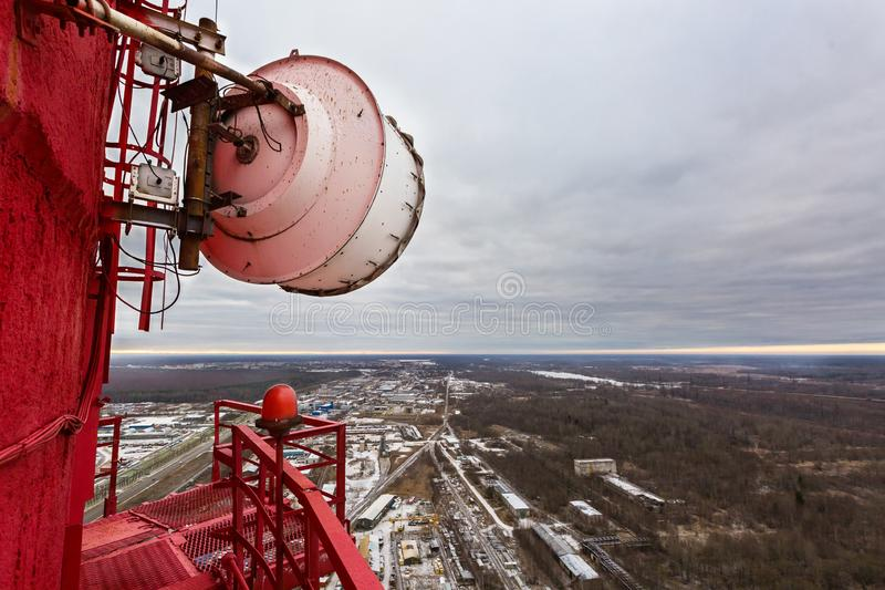 High red chimney of power plant with outdoor telecommunication high capacity microwave gear and huge radio antenna in cloudy day. royalty free stock images