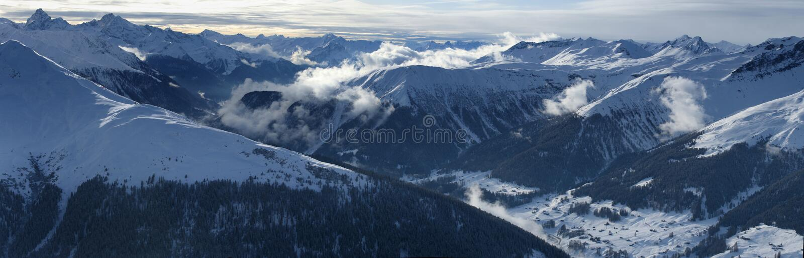 High Resolution Alpine Panorama. Very high resolution alpine panorama showing snow covered mountains and dramatic clouds royalty free stock photo