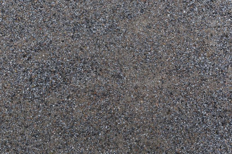 Background of wet sandy ground with gravel. High resolution full frame textured background of wet sandy ground with gravel, viewed from above royalty free stock photos