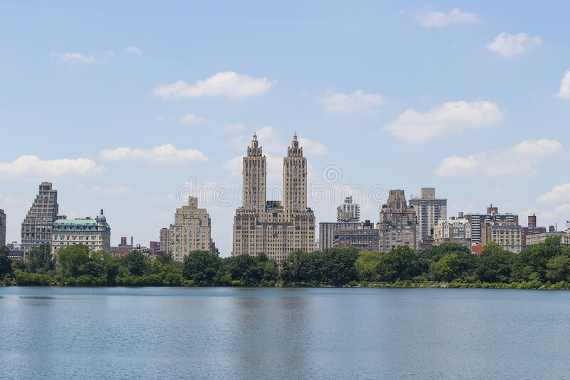 High resolution panorama of the Central Park West skyline and the Jacqueline Kennedy Reservoir in New York City with apartment. Skyscrapers over lake with royalty free stock photography