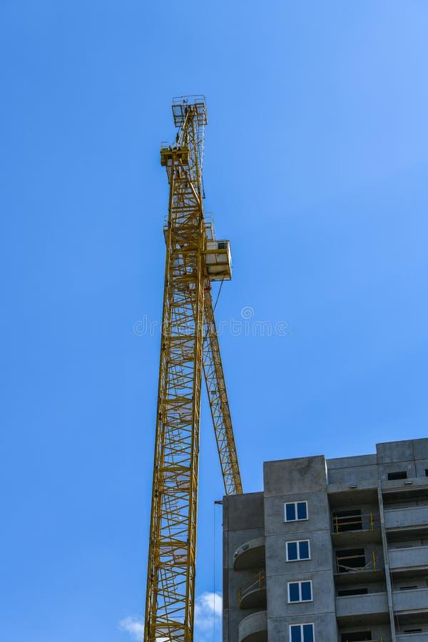 High-rise bouwkraan met een lange pijl van gele kleur tegen de blauwe hemel over de nieuwe bouw met meerdere verdiepingen van bet royalty-vrije stock afbeelding