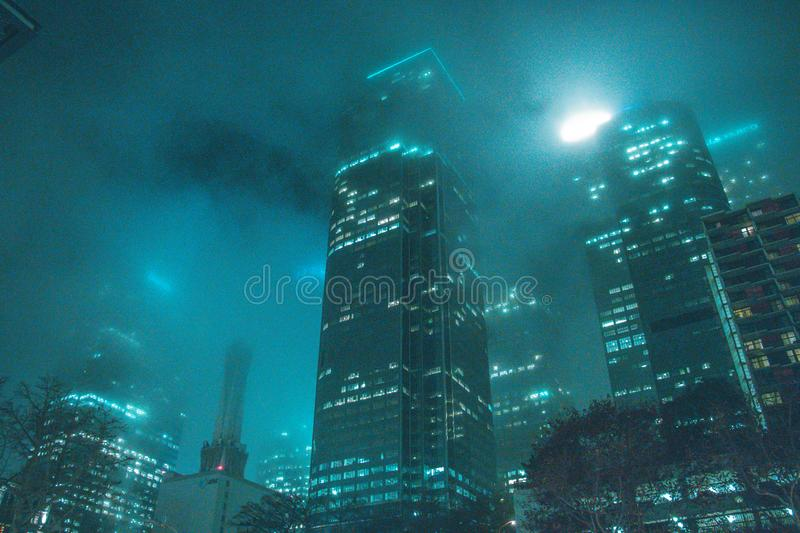 High-rise Building Beside Buildings during Night stock photography
