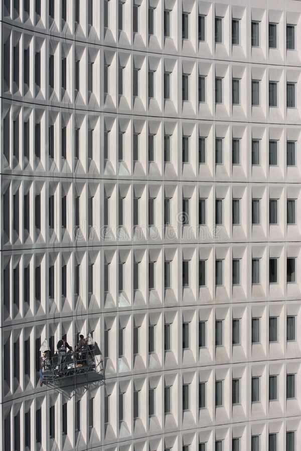 High Rise Building Maintenance. Two building maintenance staff working on a modern multi storey building stock image