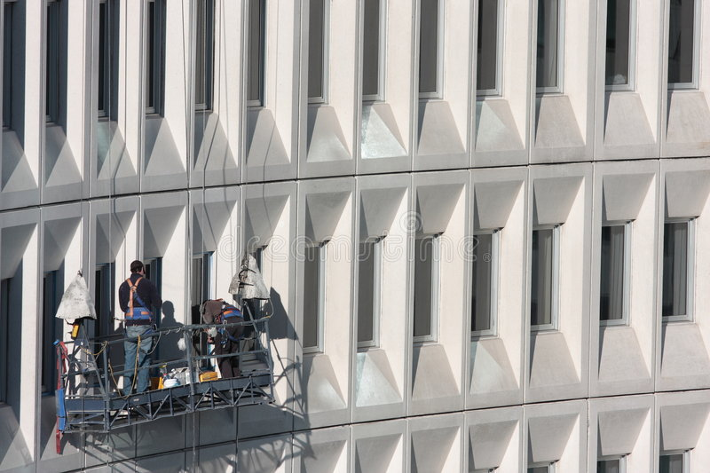 High Rise Building Maintenance. Two building maintenance staff working on a modern multi storey building royalty free stock image