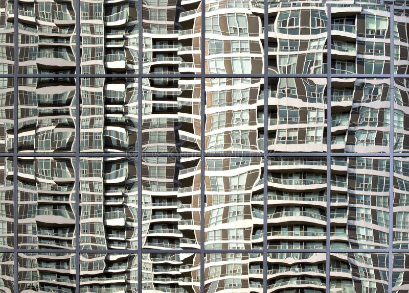 High rise building reflected in wavy glass window stock images