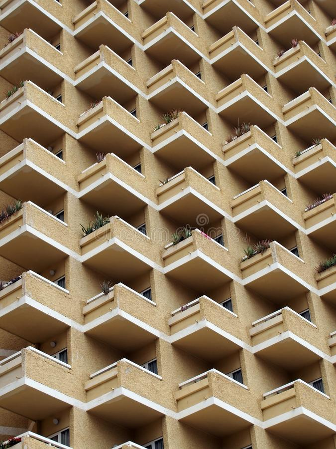 High rise building with residential flats or apartments. In a yellow concrete and brick development with balconies stock photo