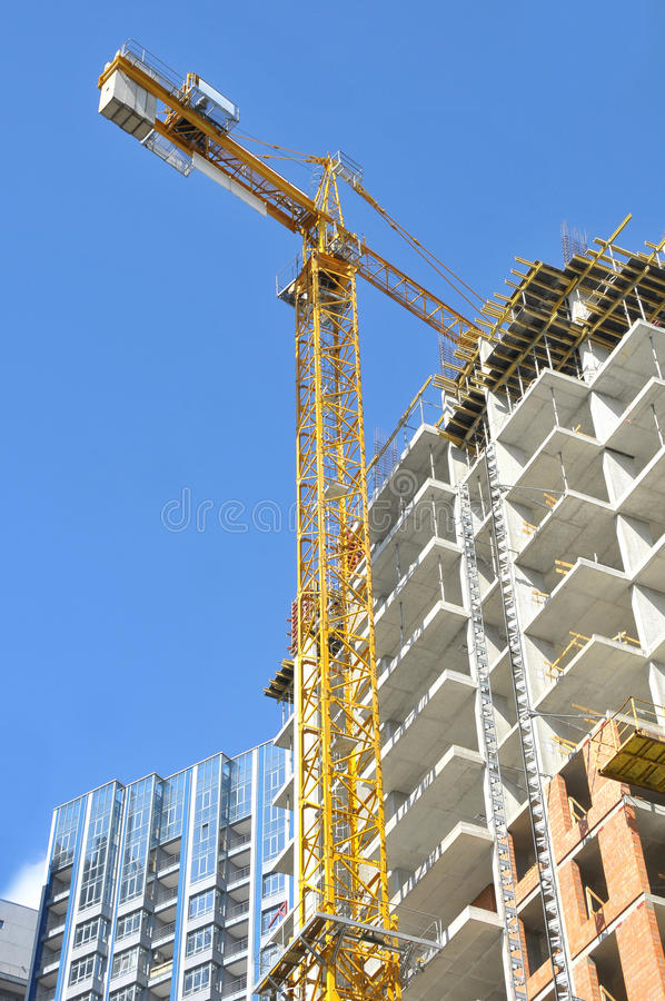 High-rise building under construction with tower crane royalty free stock photo