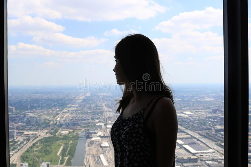 high rise building window silhouette of a young woman looking out the window at a suburban metropolis langscape with day blue sky stock photos