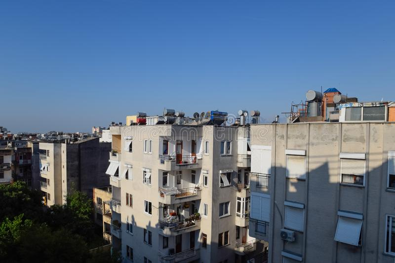 High-rise buildings in Antalya with barrels for water heating on the roof and sun blinds on the. Antalya, Turkey - May 19, 2019: High-rise buildings in Antalya royalty free stock photos