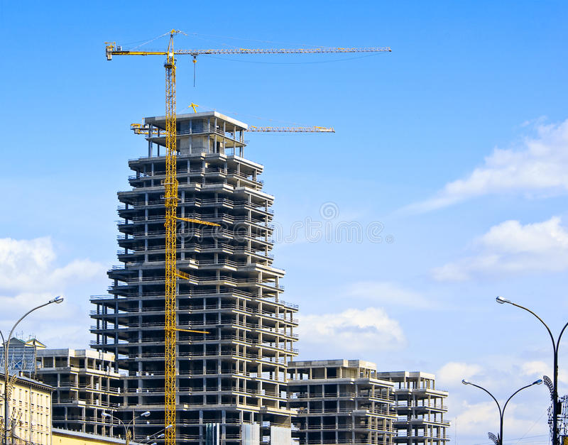 High-rise construction. Modern high-rise building with two tower cranes royalty free stock image