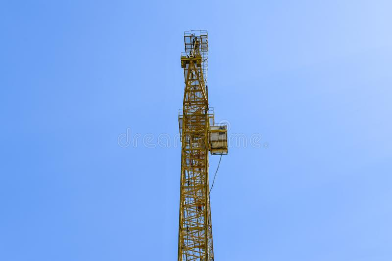 High-rise construction crane with a long arrow of yellow color against the blue sky over a new multi-storey building of concrete stock photo
