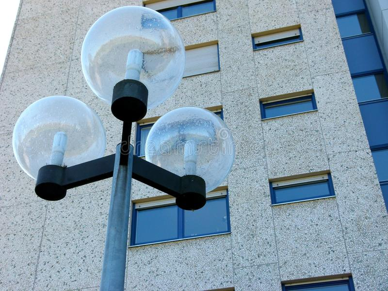 High-rise facade with modern street lamp in the foreground. Modern living, anonymous living, concrete facade with windows, street lamp with glass balls, high stock photos