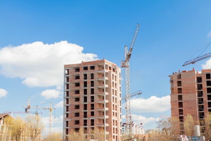 High-rise multi-storey buildings under construction. Tower cranes near building. Activity, architecture, development process, stock photos