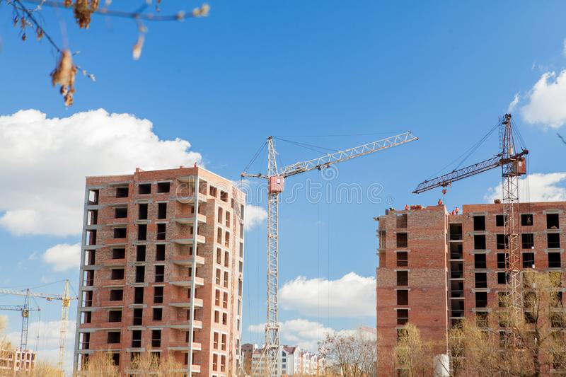 High-rise multi-storey buildings under construction. Tower cranes near building. Activity, architecture, development process,. Skyscraper royalty free stock image