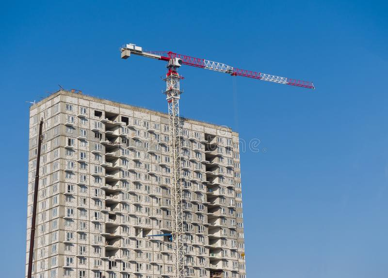 A high-rise residential building is being built. The high-rise tower crane works royalty free stock images