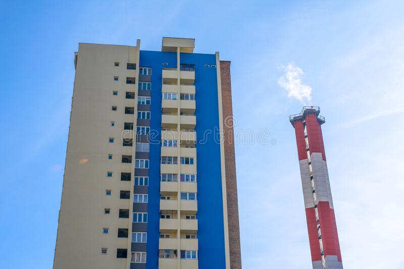 High rise residential building and industrial chimney emitting steam or smoke against blue sky. View from the bottom up. Modern problem of air and stock image