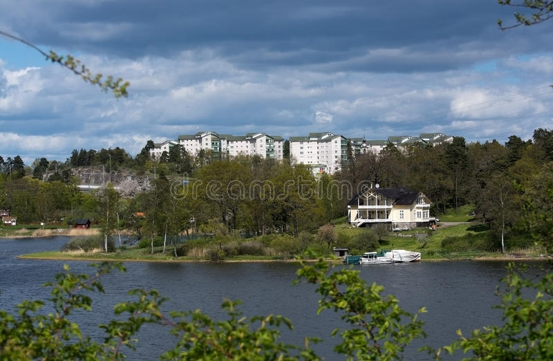 High rise residential buildings. BERGSHAMRA, STOCKHOLM, SWEDEN - MAY 8, 2015: High rise residential buildings contrasting with old small residential wooden home royalty free stock image