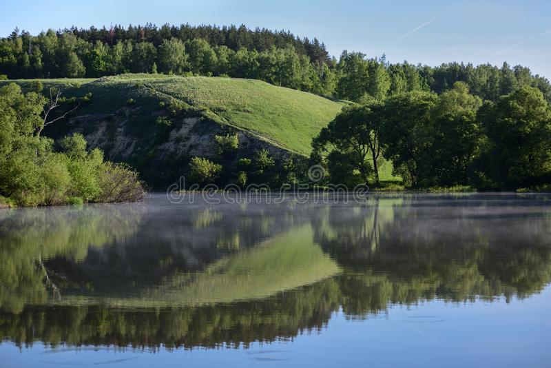 High river bank reflecting in calm waters in sunny summer day. Landscape stock images