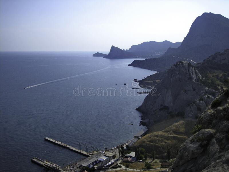 The high rock mass of the coastal mountains forms an uneven coastline of the sea.  royalty free stock photo