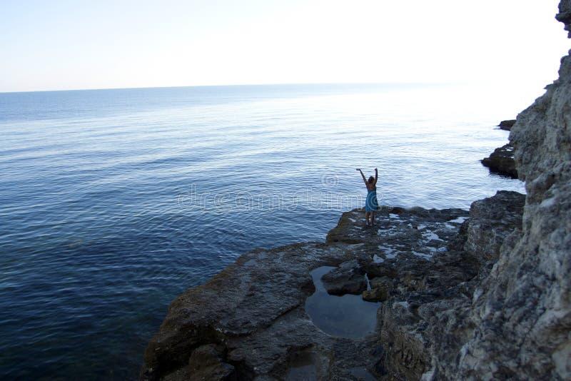 High rocks ashore and woman stock image