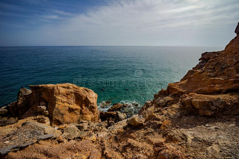 High rocky coast and sea waves of the Mediterranean sea. Top view of the coastline royalty free stock image