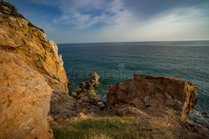 High rocky coast and sea waves of the Mediterranean sea. Top view of the coastline stock image