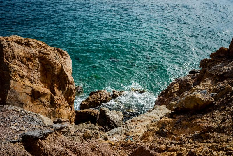 High rocky coast and sea waves of the Mediterranean sea. Top view of the coastline stock images