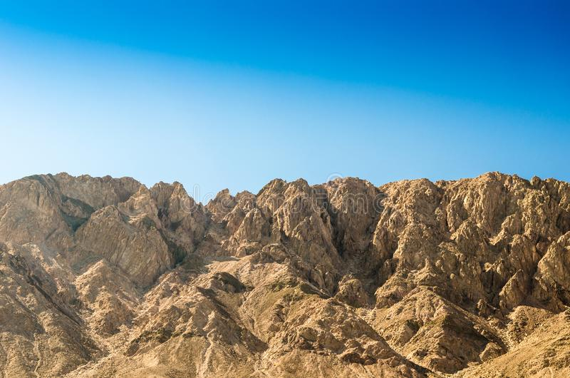 High rocky mountains against a clear blue sky. Peaks high rocky mountains against a clear blue sky stock photo