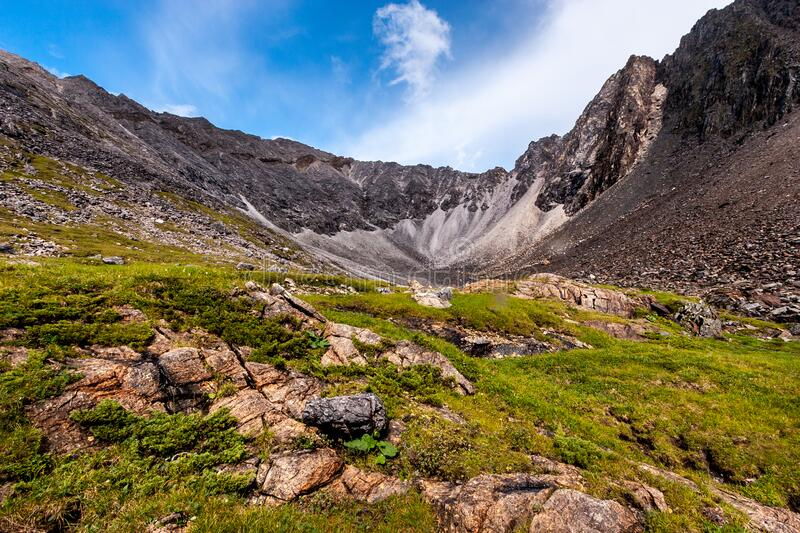High rocky ridge and large stones in the foreground. Green grass on the ground. Blue sky with clouds. Horizontal royalty free stock images