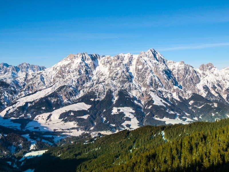 High rocky snowy peak on sunny winter day with blue sky. Alpine mountain ridge.  royalty free stock photography