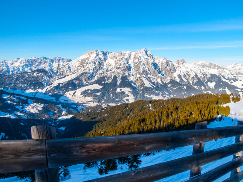 High rocky snowy peak on sunny winter day with blue sky. Alpine mountain ridge.  stock photo