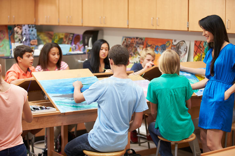 High School Art Class With Teacher. Talking To Young Female Pupil stock photo