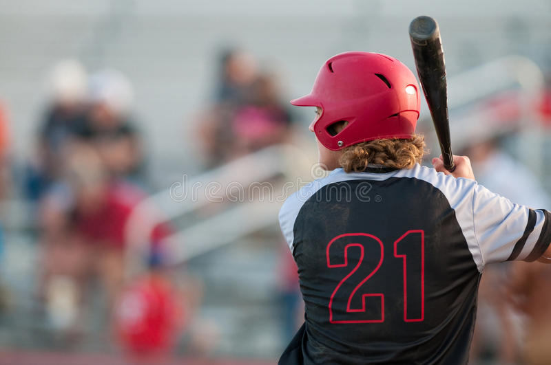 High school baseball player with long hair batting. American teen baseball player with copy space holding bat and wearing helmet stock photos