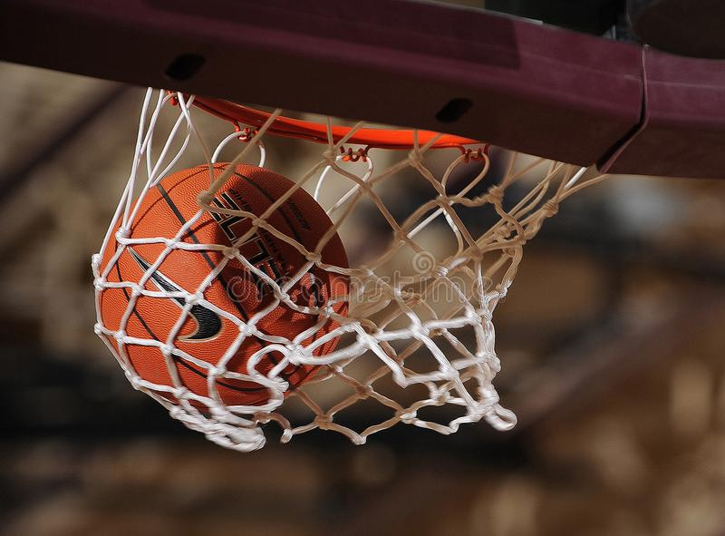 Basketball Going Through A Basketball Hoop. High School basketball game with a ball going through the hoop and net for basket royalty free stock photography