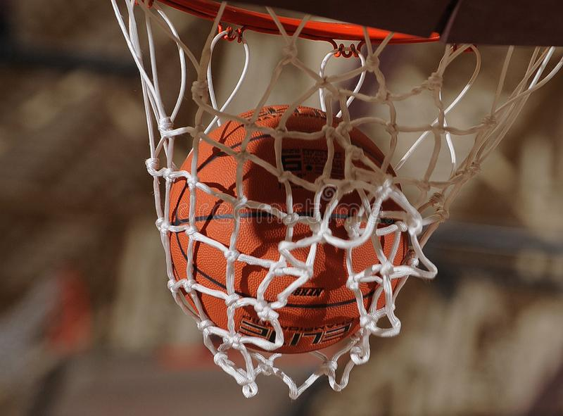Basketball Going Through A Basketball Hoop. High School basketball game with a ball going through the hoop and net for basket stock image