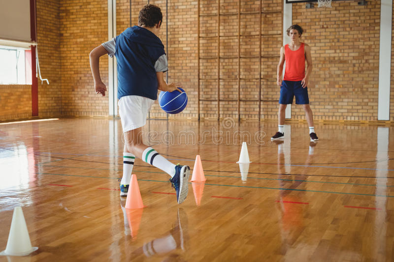 High school boys practicing football using cones for dribbling drill. In the court stock image
