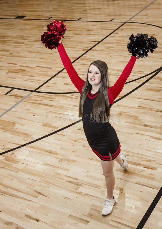 High School cheerleader at a Basketball Game. A cute cheerleader leading cheers at a high school basketball game. Lots of copy space royalty free stock photography