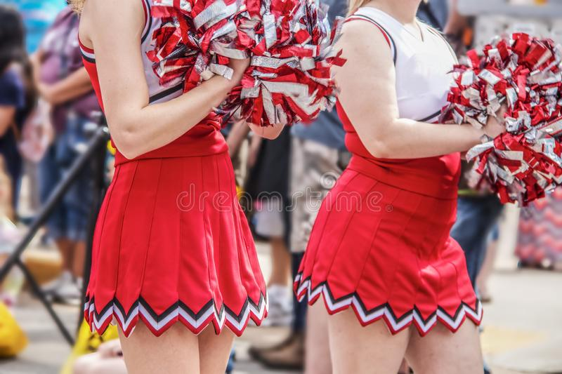 High school cheerleaders with pompoms an shirt red and white uniforms in parade with blurred crowd in the background - cropped and royalty free stock images