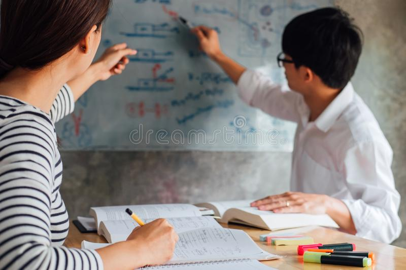 High school or college student group catching up workbook and learning tutoring in classroom and reading, doing homework and. Lesson practice preparing exam to stock image