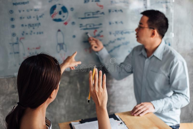 High school or college student group catching up workbook and learning tutoring in classroom and reading, doing homework and royalty free stock images